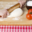 Rolling pin kneading on pizza dough — Stock Photo