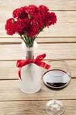 Röd blomma och vin inrett på bord — Stockfoto