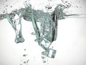 Ice cubes dropped in water — Stock Photo