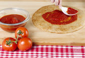 Pizza dough with red sauce and tomatoes — Stock Photo
