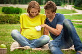 Young pregnant woman with young man on picnic — Stock Photo