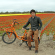 Tourist on a orange bike at the flower fields in the Netherlands — Stock fotografie
