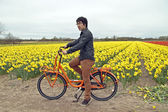 Tourist on a orange bike at the flower fields in the Netherlands — Stock Photo