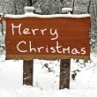 Merry Christmas written on a snowy wooden sign in winter — Stock Photo #11278520