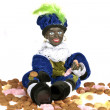 Black Piet sitting on a bag with gingernuts and candies — Stock Photo #11305741