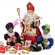 Traditional dutch culture: Santa Claus with his two black pieten with gingernuts and sweets at the 5th of december — Stock Photo