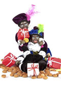 Two black Piet with a bag full of gingernuts and candies — Stock Photo