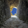 Going to the light: tunnel in a rock towards the blue sky in Portugal — Stock Photo #11448300