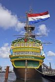 VOC ship in Amsterdam harbor the Netherlands with the dutch national flag — Stock Photo