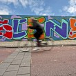 Amsterdam streetscenery: Biker biking along a graffiti wall in the Netherlands - Stock Photo