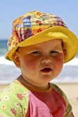 Cute little baby girl sitting in the sand at the beach — Stock Photo