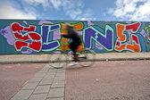 Amsterdam streetscenery: Biker biking along a graffiti wall in the Netherlands — Stock Photo