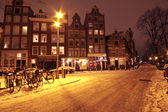 Cityscenic from Amsterdam covered with snow in the Netherlands at night — Stock Photo