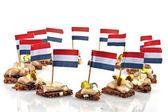 Typical dutch: Rye bread with raw herring and onions with the dutch flag — Stock Photo