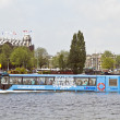 Floating bus is cruising through Amsterdam canals - Stock Photo