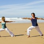 jovem casal fazendo exercícios de ioga na praia — Foto Stock