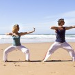 Young couple doing yoga exercises at the beach — Stock Photo