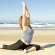 Young healthy woman doing yoga exercises at the beach — Stock Photo