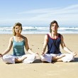 Couple meditating at the beach — Stock Photo