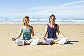 Dvojice medituje na pláži — Stock fotografie