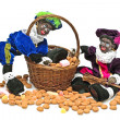 Two black piet with a basket full of gingernuts and sweets — Stock Photo