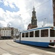Driving tram in front of the Munt tower in Amsterdam the Netherl - Stock Photo