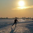 Ice skating in the countryside from the Netherlands at sunset — Stock Photo #12169564