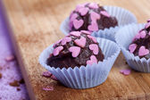 Chocolate pralines with pink hearts — Stock Photo