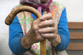 Hands of an old woman with a cane — Stock Photo
