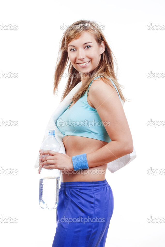 Young woman in sports outfit holding a bottle of water smiling - islotad on white — Stock Photo #11336398