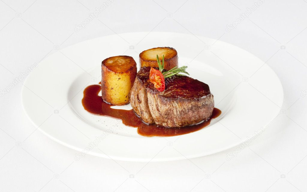 Beef filet with fondant potato and red wine sauce on a white plate — Stock Photo #11338349