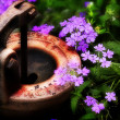 Rusty pump among the flowers — Stock Photo