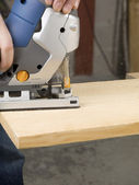 Person cutting wooden plank with jigsaw cutter — Stock Photo