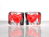Two red hearts frozen in ice — Stock Photo