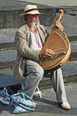 Colorful man in traditional dress playing the bandura — Stock Photo