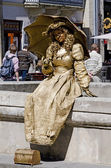 Living statue - girl with an umbrella — Stock Photo