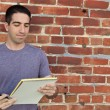 Stock Photo: Cute guy using paper pad by brick wall
