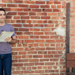 Cute man writing on paper pad by brick wall — ストック写真