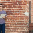 Cute man writing on paper pad by brick wall — Stock fotografie