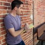 χαριτωμένο άνθρωπος γραπτώς σε χαρτί μαξιλάρι από τοίχο από τούβλα — Φωτογραφία Αρχείου