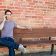 Guy sitting on bench talking on the phone — Stock Photo