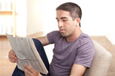 Attractive guy reading newspaper — Stock Photo