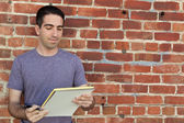 Cute guy using paper pad by brick wall — Stock Photo