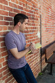 Cute man writing on paper pad by brick wall — Stock Photo