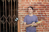 Guy smiling with paper against brick wall — Stock Photo
