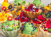Colorful cup cakes with confetti — Stock Photo