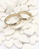Wedding rings on the white hearts background — Stock Photo