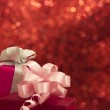 Gift boxes with bows on the red shiny background — Stock Photo #11262171