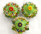 Tree green cup cakes on the white textile — Stock Photo