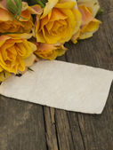 Blank note on the old table with yellow roses — Stock Photo